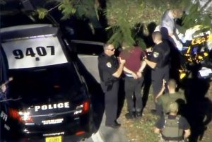 A man placed in handcuffs is led by police near Marjory Stoneman Douglas High School following a shooting incident in Parkland, Florida, February 14, 2018 in a still image from video. WSVN.com via REUTERS
