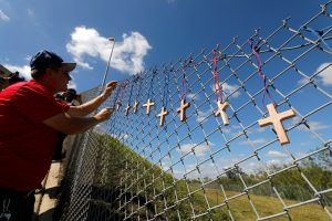 Bob Ossler, chaplain with the Cape Coral volunteer fire department, places seventeen crosses for the victims of yesterday's shooting at Marjory Stoneman Douglas High School on a fence a short distance from the school in Parkland, Florida, February 15, 2018.