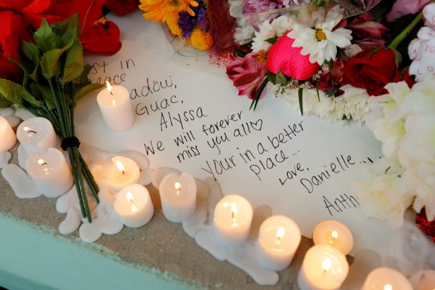 A handwritten note to a lost friend is surrounded by candles and flowers at a candlelight vigil the day after a shooting at Marjory Stoneman Douglas High School in Parkland, Florida, February 15, 2018. REUTERS/Jonathan Drake