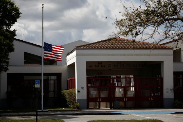 A flag flies at half mast next to the entrance of the Marjory Stoneman Douglas High School, after the police security perimeter was removed. REUTERS/Carlos Garcia Rawlins