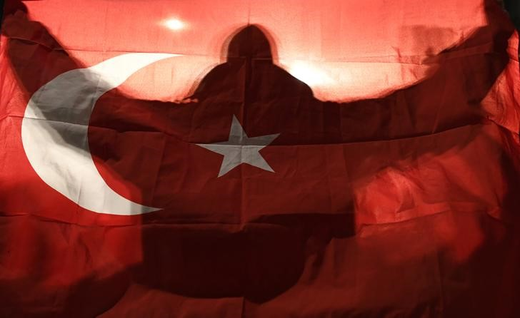A demonstrator holds a Turkish flag outside the Turkish consulate in Rotterdam where a crowd gathered to await the arrival of the Turkish Family Minister Fatma Betul Sayan Kaya, who decided to travel to Rotterdam by land after Turkish Foreign Minister Mevlut Cavusoglu's flight was barred from landing by the Dutch government, in Rotterdam, Netherlands March 11, 2017. REUTERS/Dylan Martinez