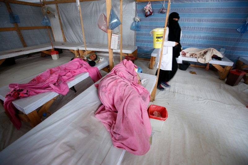 FILE PHOTO: A nurse walks by women being treated at a cholera treatment center in the Red Sea port city of Hodeidah, Yemen October 8, 2017. REUTERS/Abduljabbar Zeyad