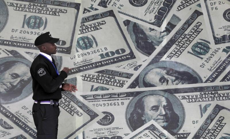 FILE PHOTO: A security guard walks past a montage of U.S. $100 dollar bills outside a currency exchange bureau in Kenya's capital Nairobi, July 23, 2015. REUTERS/Thomas Mukoya/File Photo