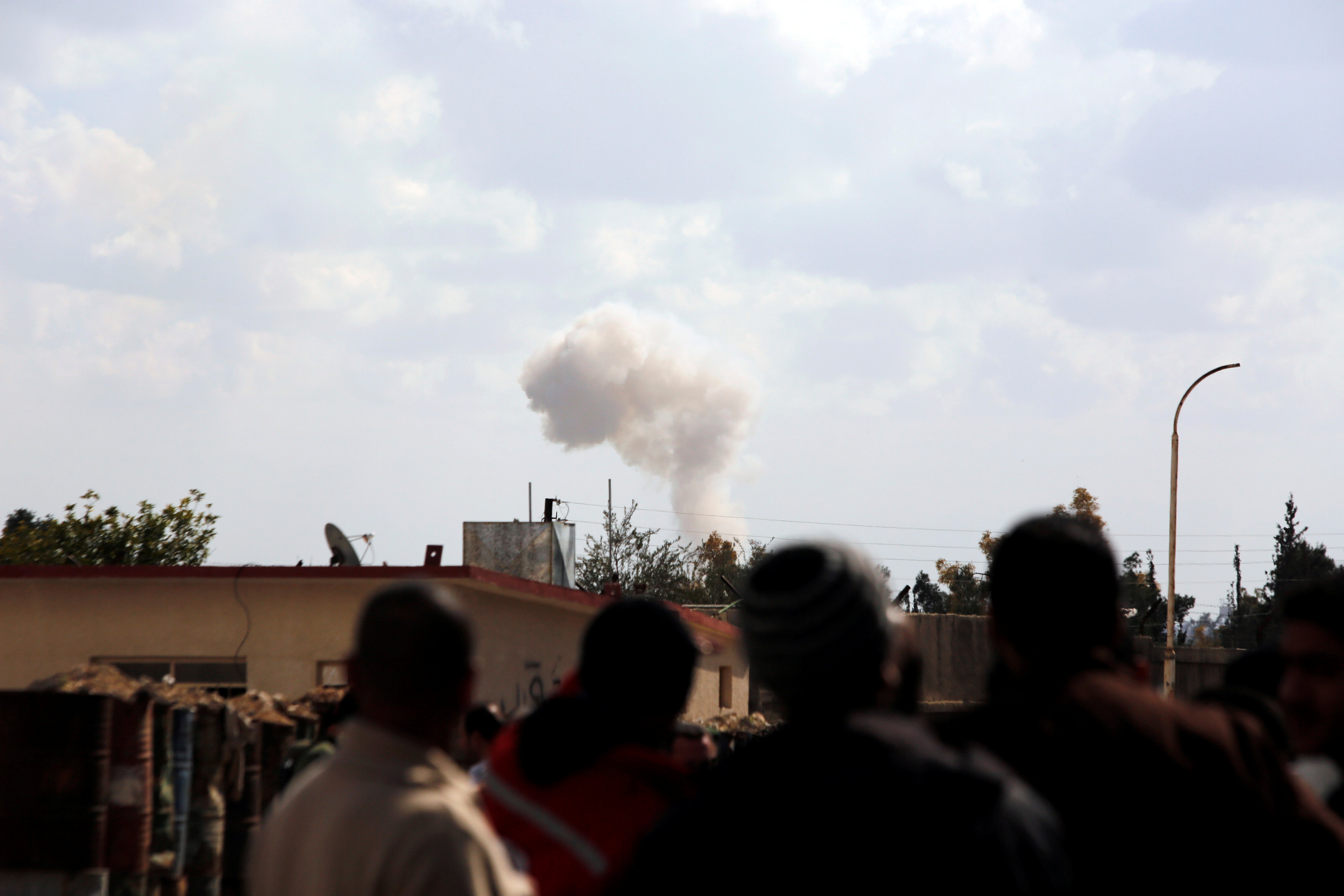 People watch as smoke rises in eastern Ghouta, Damascus, Syria February 28, 2018. REUTERS/Omar Sanadiki