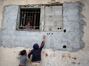 Palestinian children play as a girl held by her mother looks out of the window of house in the northern Gaza Strip February 12, 2018. REUTERS/Mohammed Salem