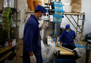 Palestinians work at Wael Al-Wadiya's snacks and chips factory, east of Gaza City February 19, 2018. REUTERS/Mohammed Salem