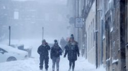 People walk along the street through the snow near Sterling Castle, Scotland, Britain, March 1, 2018. REUTERS/Russell Cheyne