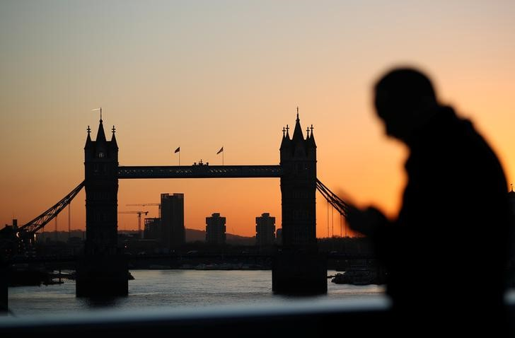 A man walks across London Bridge as the sun rises behind Tower Bridge in London, Britain, January 19, 2018. REUTERS/Hannah McKay