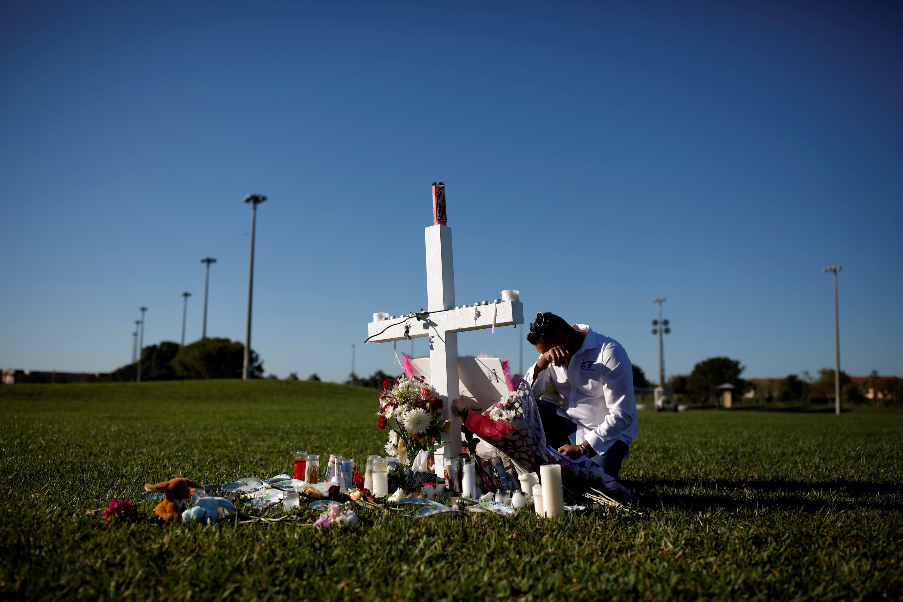Joe Zevuloni mourns in front of a cross placed in a park to commemorate the victims of the shooting at Marjory Stoneman Douglas High School, in Parkland, Florida, U.S., February 16, 2018. REUTERS/Carlos Garcia Rawlins