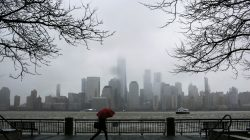 A woman walks during rain while the New York skyline and the One World Trade Center are seen from Exchange Place in New Jersey, U.S., March 7, 2018. REUTERS/Eduardo Munoz