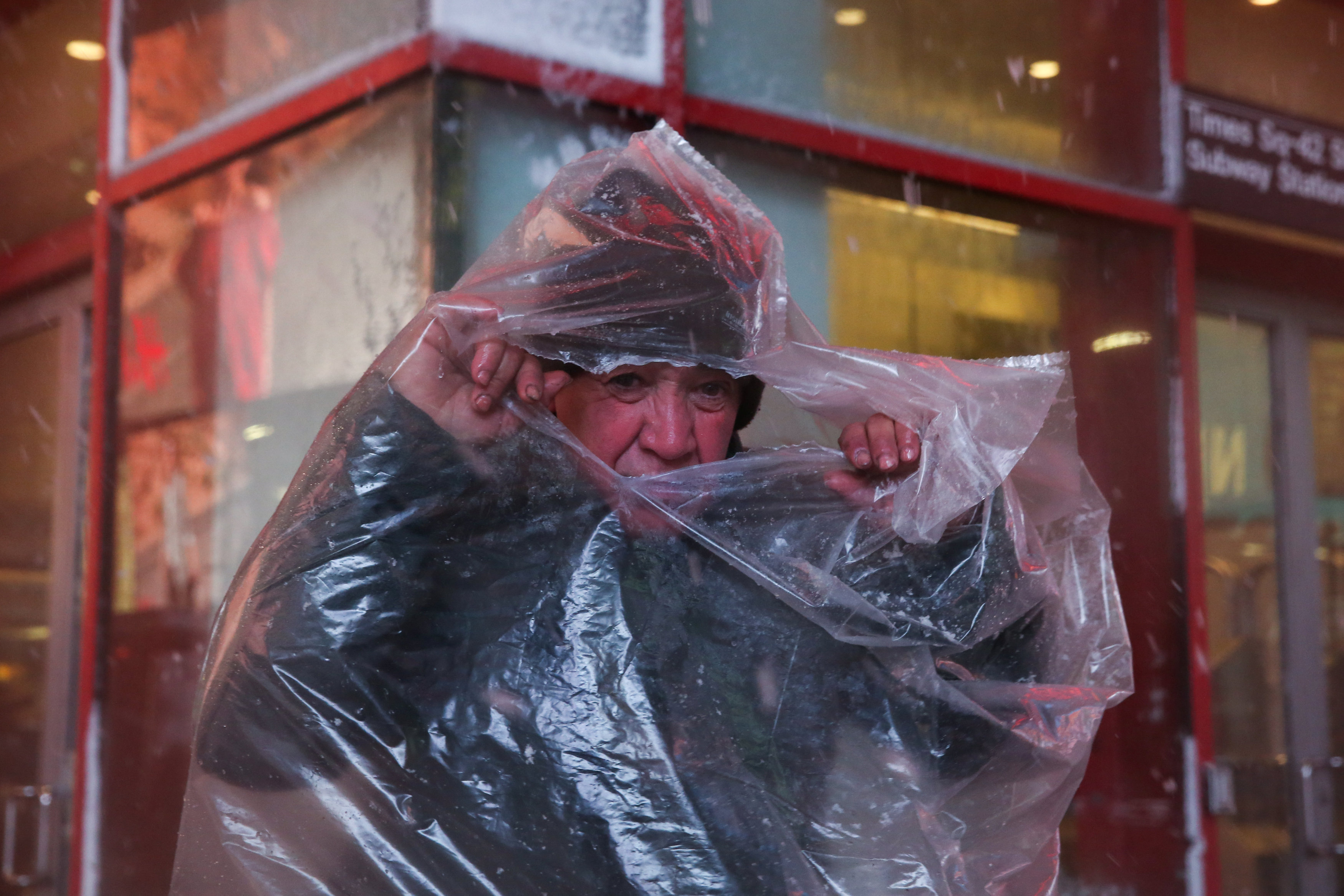 A man takes shelter as snow falls in Times Square in Manhattan in New York City, New York, U.S., March 7, 2018. REUTERS/Amr Alfiky