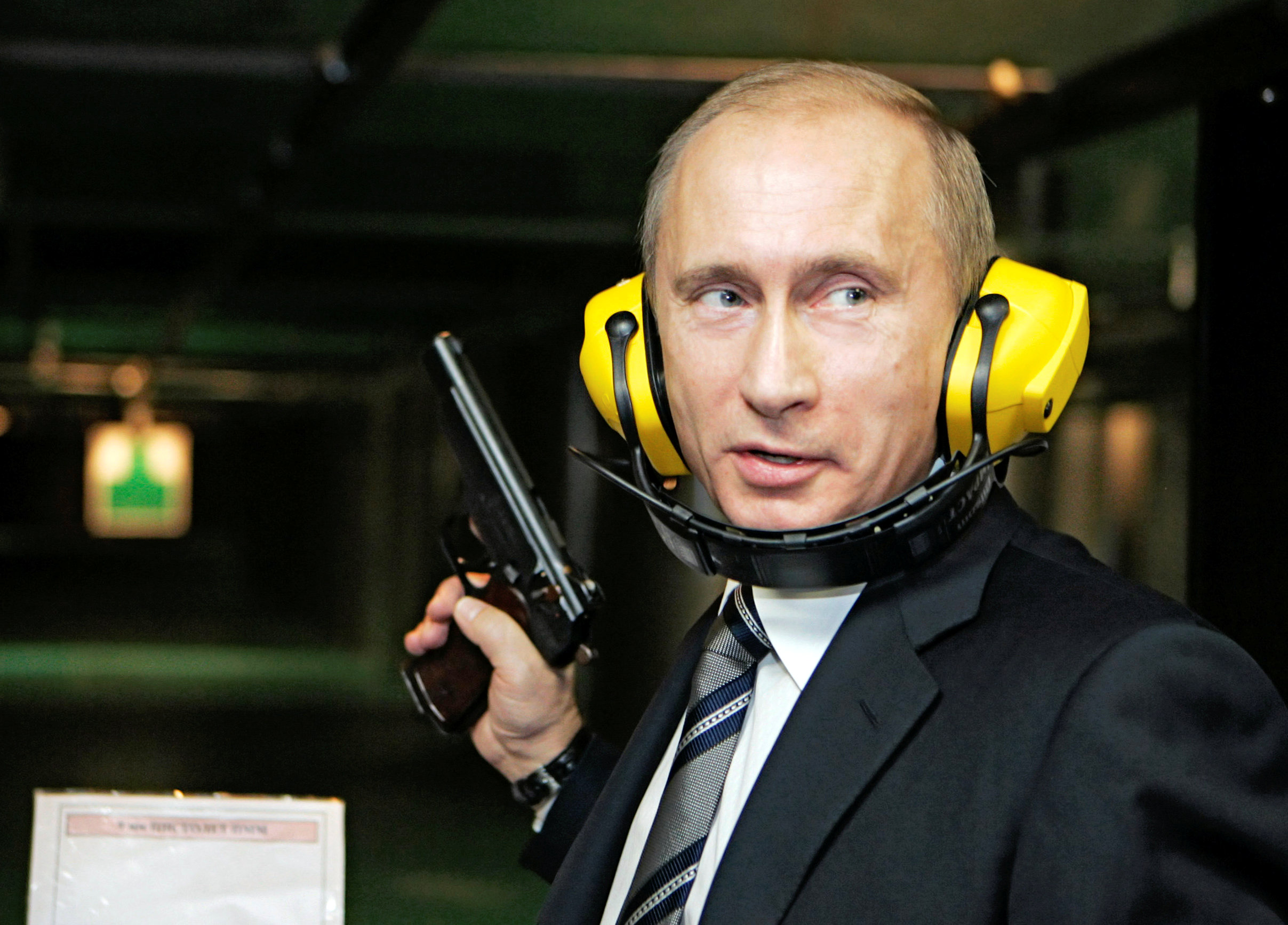 FILE PHOTO: Russian President Vladimir Putin stands with a gun at a shooting gallery of the new GRU military intelligence headquarters building as he visits it in Moscow November 8, 2006.