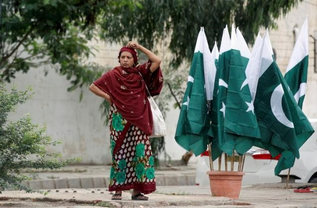 A woman adjusts her scarf as she waits for a bus next to a stall with national flags, ahead of Pakistan's Independence Day, in Karachi, Pakistan August 2, 2017. REUTERS/Akhtar Soomro