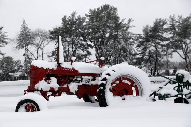 A tractor stands covered in snow during a snowstorm in Huntington, New York, U.S., March 13, 2018. REUTERS/Shannon Stapleton