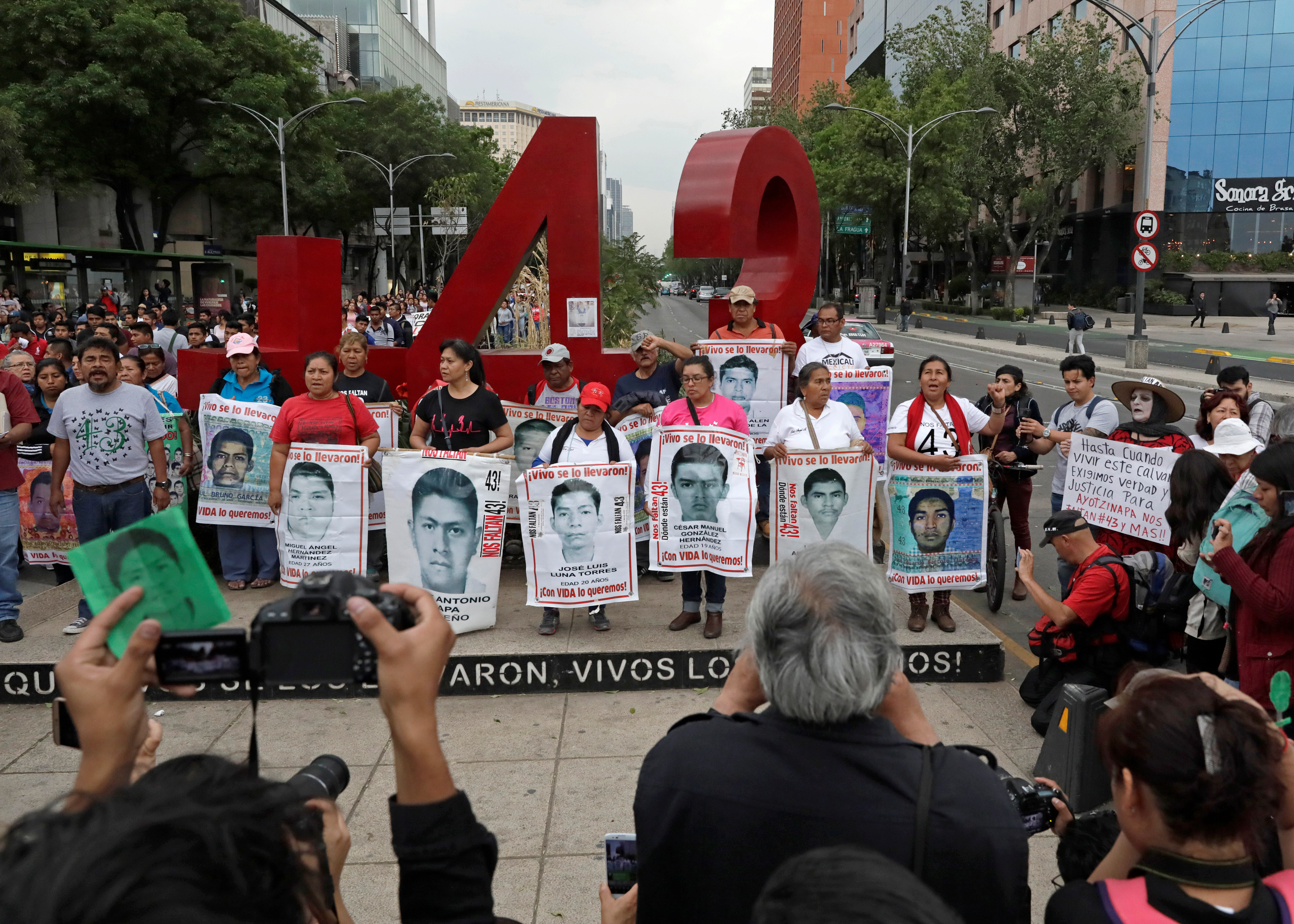 FILE PHOTO: Relatives pose with images of some of the 43 missing Ayotzinapa College Raul Isidro Burgos students in front of a monument of the number 43, during a march to mark the 41st month since their disappearance in the state of Guerrero, in Mexico City, Mexico February 26, 2018. REUTERS/Henry Romero