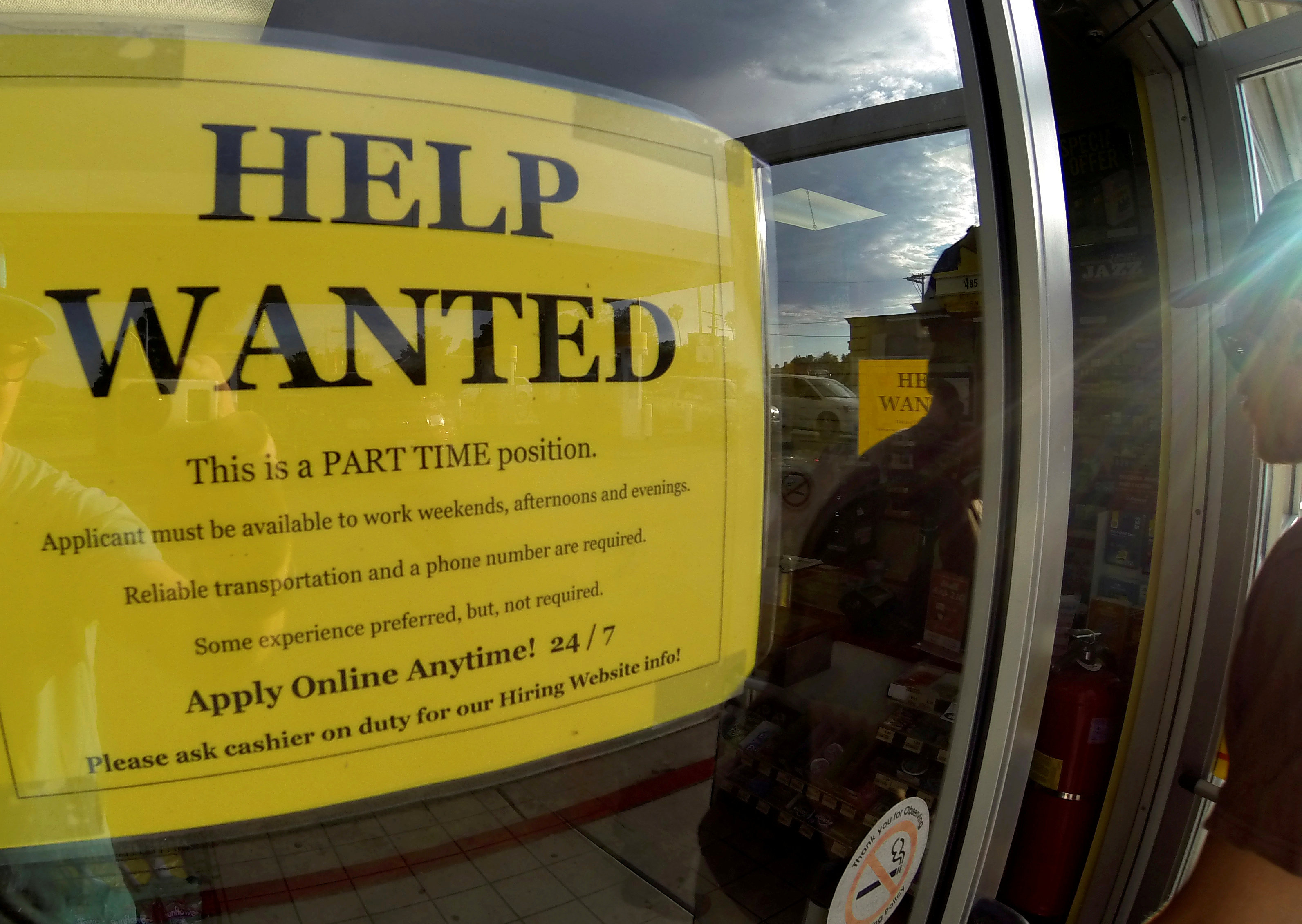 FILE PHOTO: A help wanted sign is posted on the door of a gas station in Encinitas California