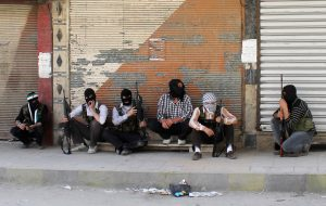 FILE PHOTO: Free Syrian Army members, with covered faces and holding weapons, sit by the side of a street in Qaboun district, Syria Damascus June 11, 2012. REUTERS/Stringer/File Photo