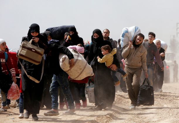 FILE PHOTO: People walk with their belongings as they flee the rebel-held town of Hammouriyeh, in the village of Beit Sawa, eastern Ghouta, Syria March 15, 2018. REUTERS/Omar Sanadiki