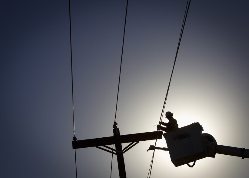 An electrical line technician works on restoring power in Vilonia, Arkansas April 29, 2014. REUTERS/Carlo Alle