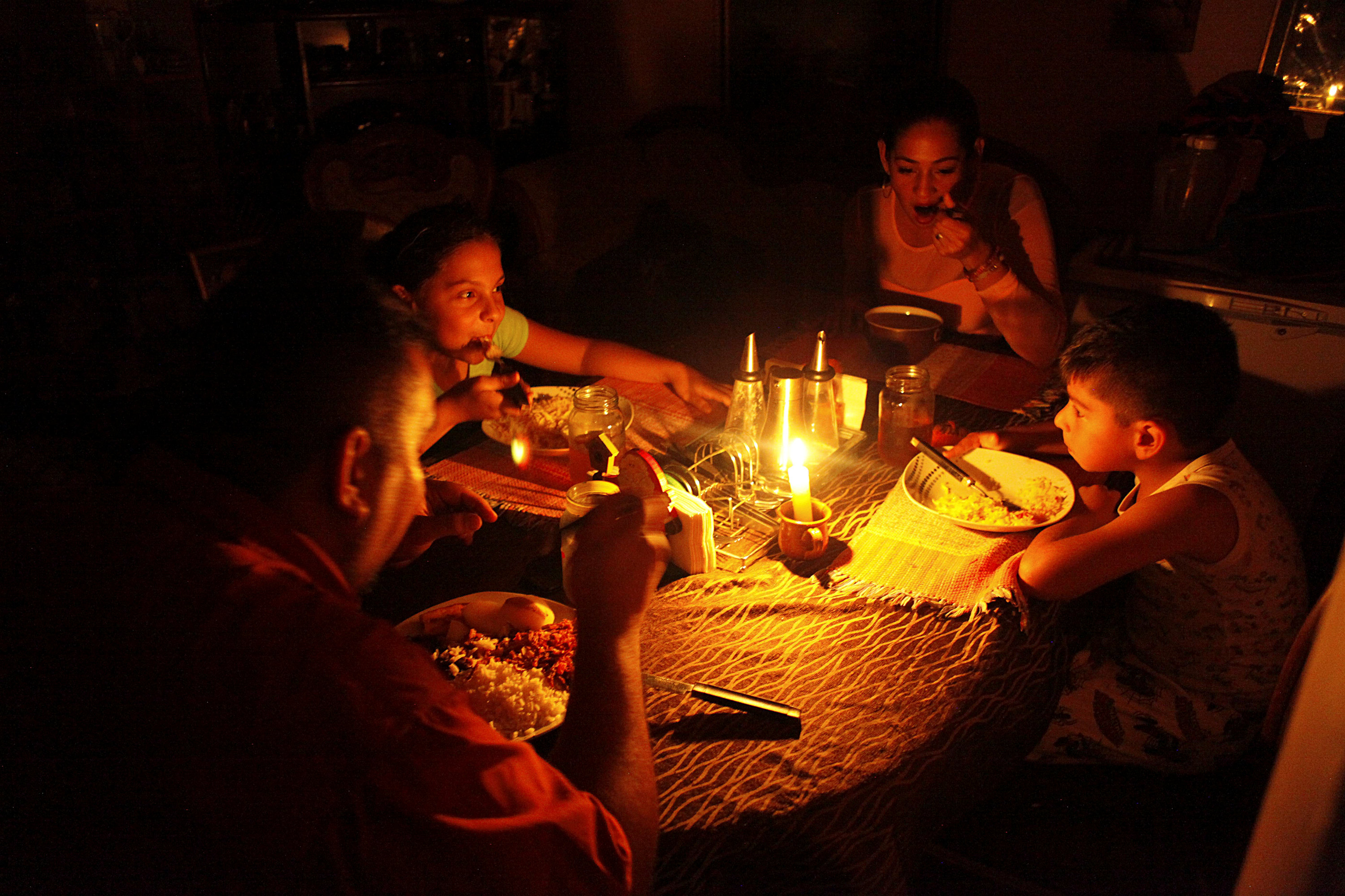Lisney Albornoz (2nd R) and her family use a candle to illuminate the table while they dine, during a blackout in San Cristobal, Venezuela March 14, 2018. Picture taken March 14, 2018. REUTERS/Carlos Eduardo Ramirez