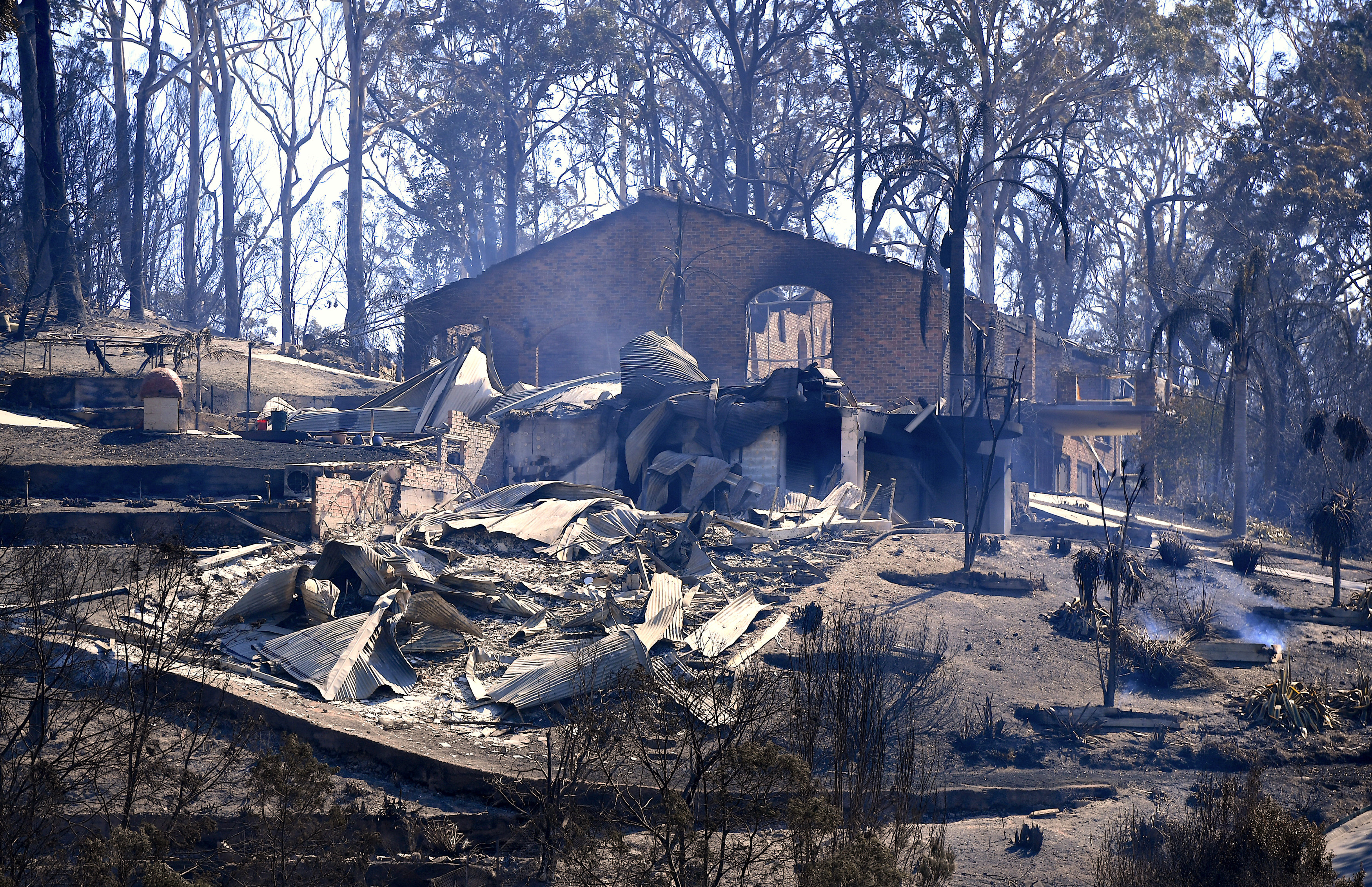 Smoke rises from a destroyed home after a bushfire swept through the town of Tathra, located on the south-east coast of New South Wales in Australia, March 19, 2018. AAP/Dean Lewins/via REUTERS
