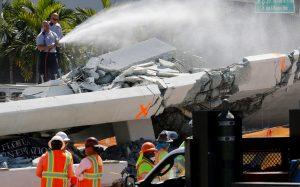 Firefighters spray water on debris from a collapsed pedestrian bridge at Florida International University in Miami, Florida, U.S., March 16, 2018. REUTERS/Joe Skipper