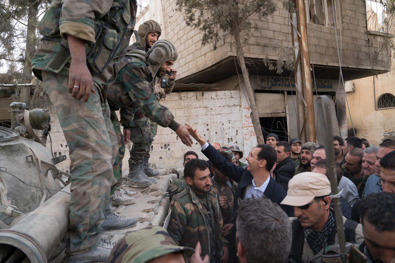 Syrian President Bashar al-Assad reaches out to shake the hand of a Syrian army soldier in eastern Ghouta, Syria, March 18, 2018. SANA/Handout via REUTERS