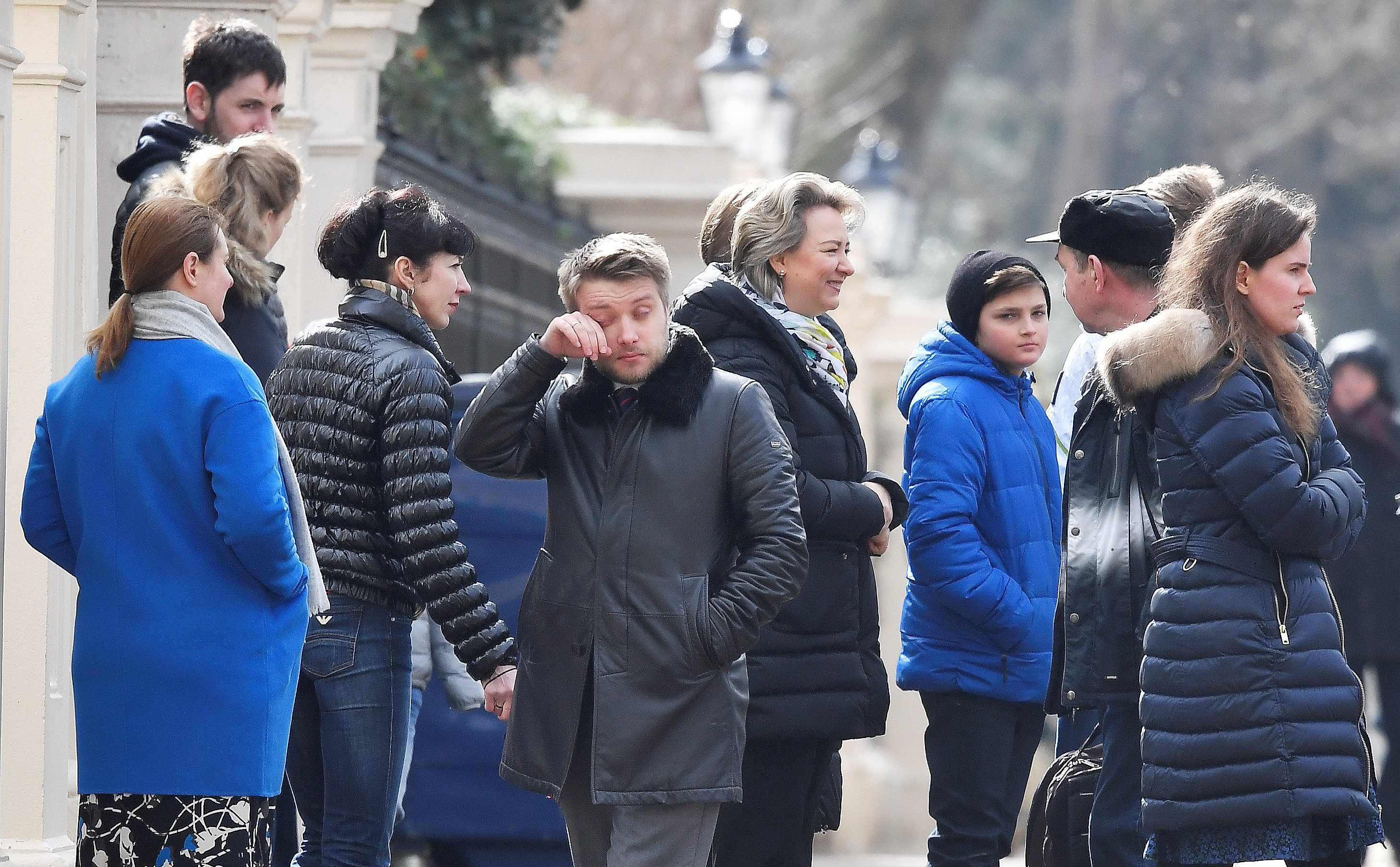 Embassy staff react as colleagues and children board buses outside Russia's Embassy in London, Britain,