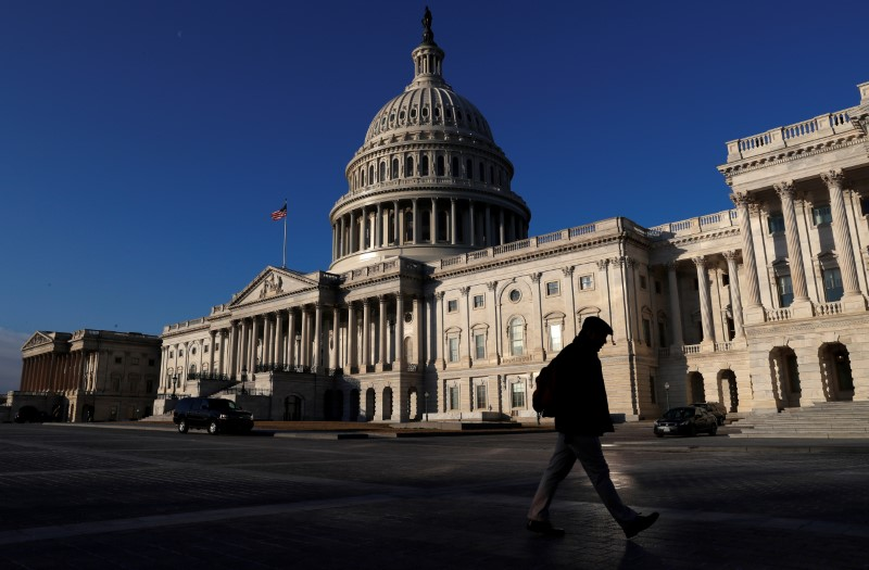 People walk by the U.S. Capitol building in Washington, U.S., February 8, 2018. REUTERS/ Leah Millis