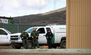 FILE PHOTO: U.S. border patrol officers are pictured near a prototype for U.S. President Donald Trump's border wall with Mexico, behind the current border fence in this picture taken from the Mexican side of the border in Tijuana, Mexico