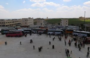 People, who were evacuated from the two rebel-besieged Shi'ite villages of al-Foua and Kefraya, stand near buses at insurgent-held al-Rashideen, Aleppo province, Syria April 19, 2017. REUTERS/Ammar Abdullah