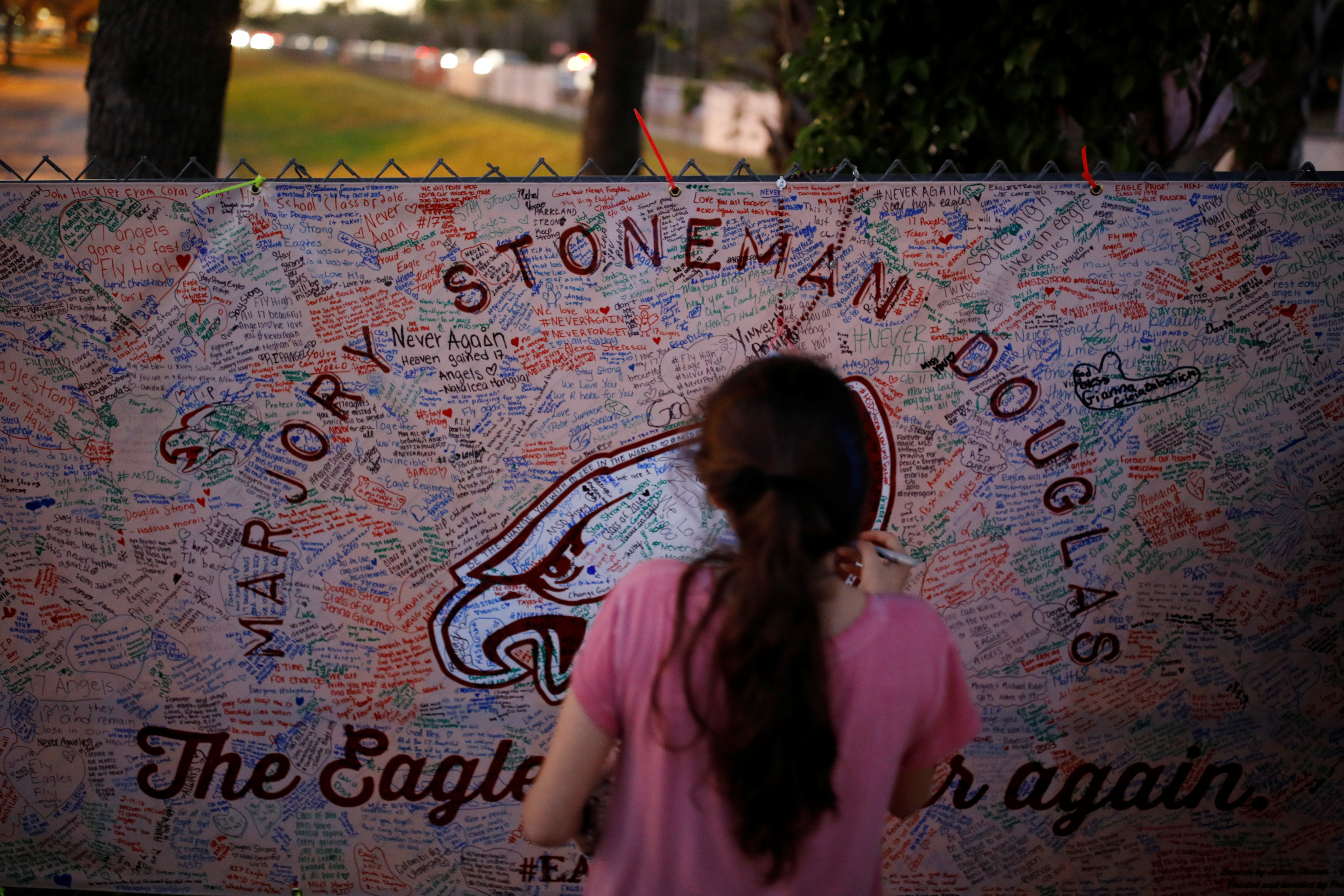 A girl writes a note on a banner placed on the fence of the Marjory Stoneman Douglas High School to commemorate the victims of the mass shooting, in Parkland, Florida, U.S., February 21, 2018. REUTERS/Carlos Garcia Rawlins