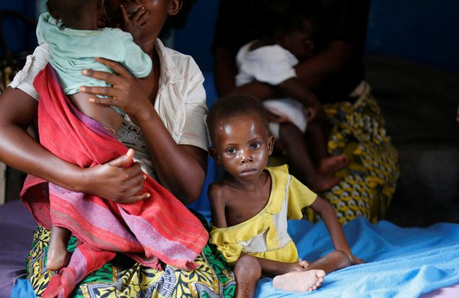 An internally displaced woman sits with her severely acute malnourished children as they wait to receive medical attention at the Tshiamala general referral hospital of Mwene Ditu in Kasai Oriental Province in the Democratic Republic of Congo, March 15, 2018. REUTERS/Thomas Mukoya