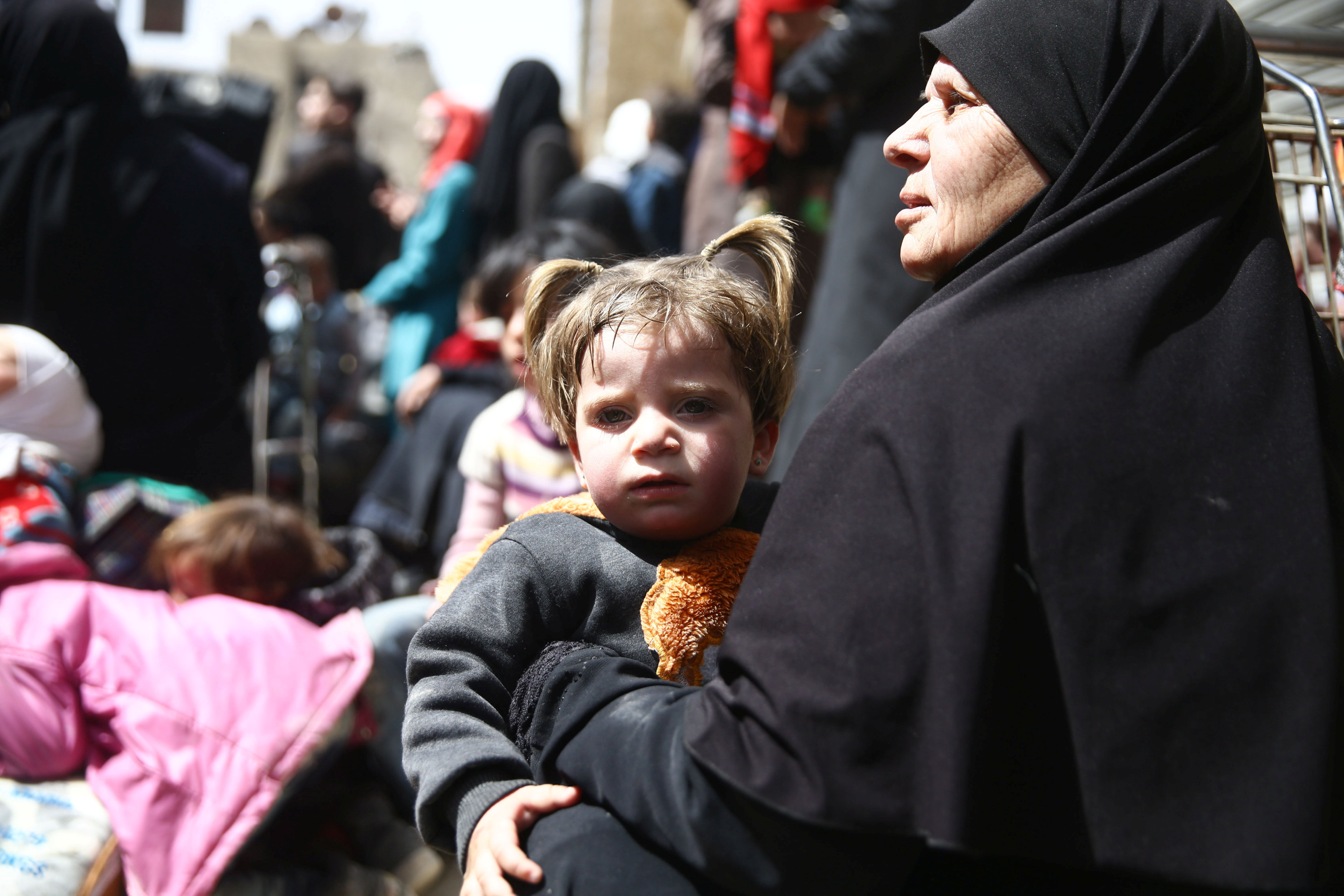 A woman holds a child during evacuation from the besieged town of Douma, Eastern Ghouta, in Damascus, Syria March 22, 2018. REUTERS/Bassam Khabieh