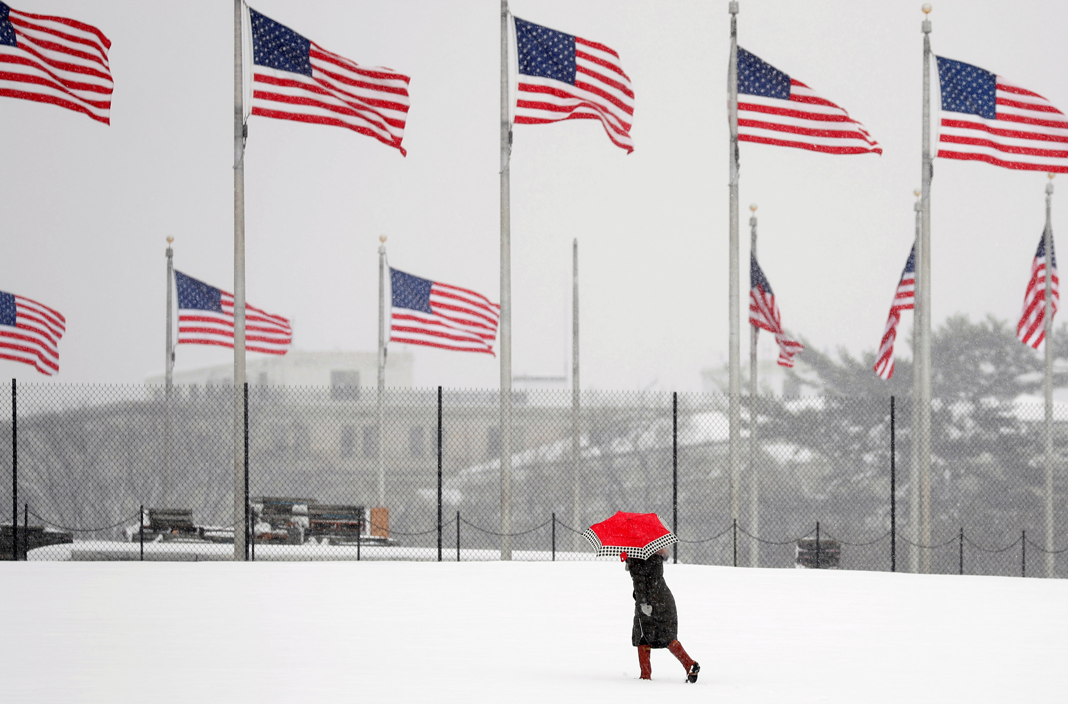 A woman holds an umbrella as she walks toward the Washington Monument during a snowstorm in Washington, U.S., March 21, 2018. REUTERS/Kevin Lamarque