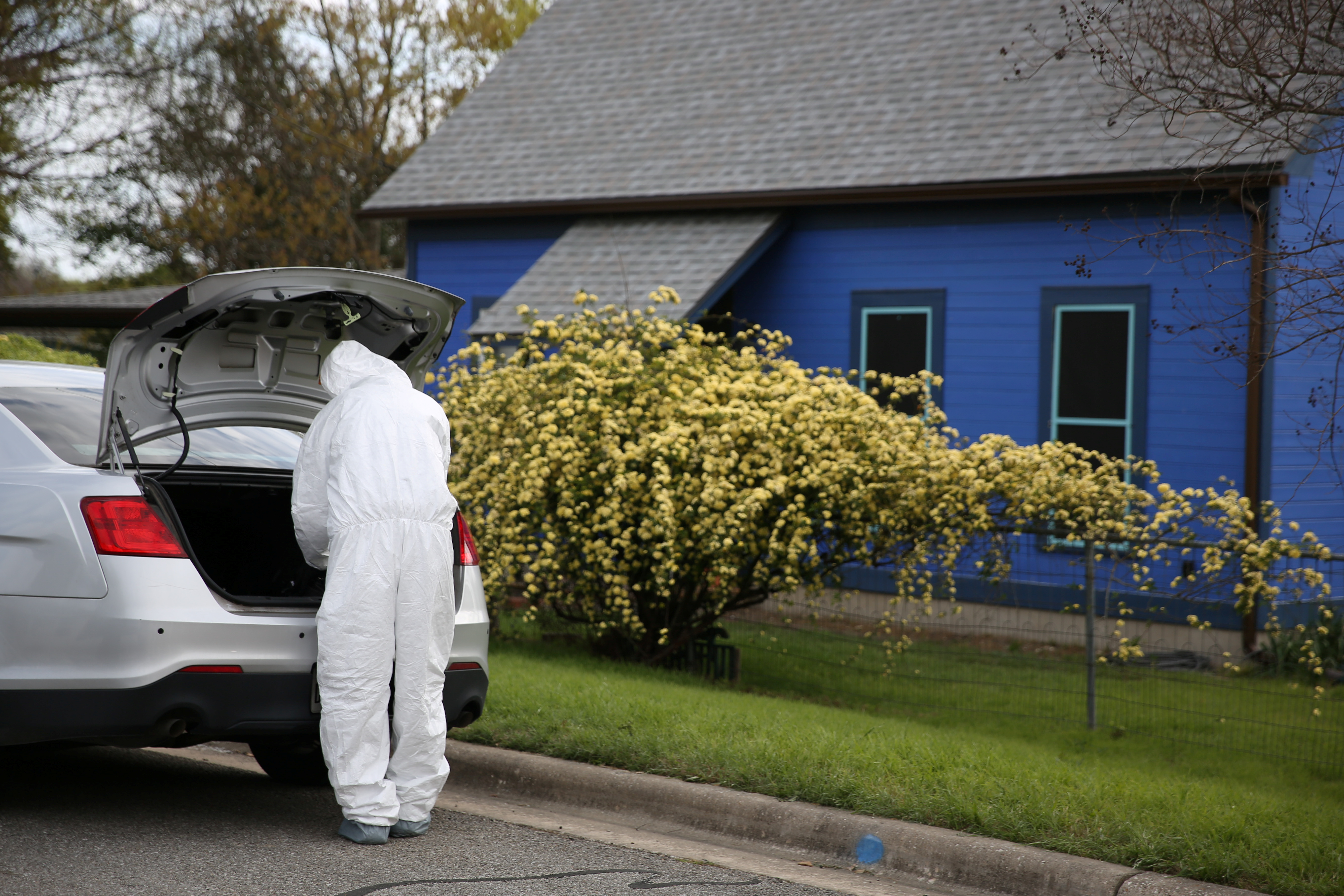 A law enforcement member is seen down the street from the home where Austin serial bomber Mark Anthony Conditt lived in Pflugerville, Texas, U.S., March 22, 2018. REUTERS/Loren Elliott