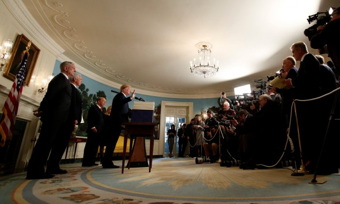 U.S. President Donald Trump speaks, as he stands next to Congress' $1.3 trillion spending bill, during a signing ceremony, in the Diplomatic Room of the White House in Washington, D.C., U.S., March 23, 2018. REUTERS/Kevin Lamarque