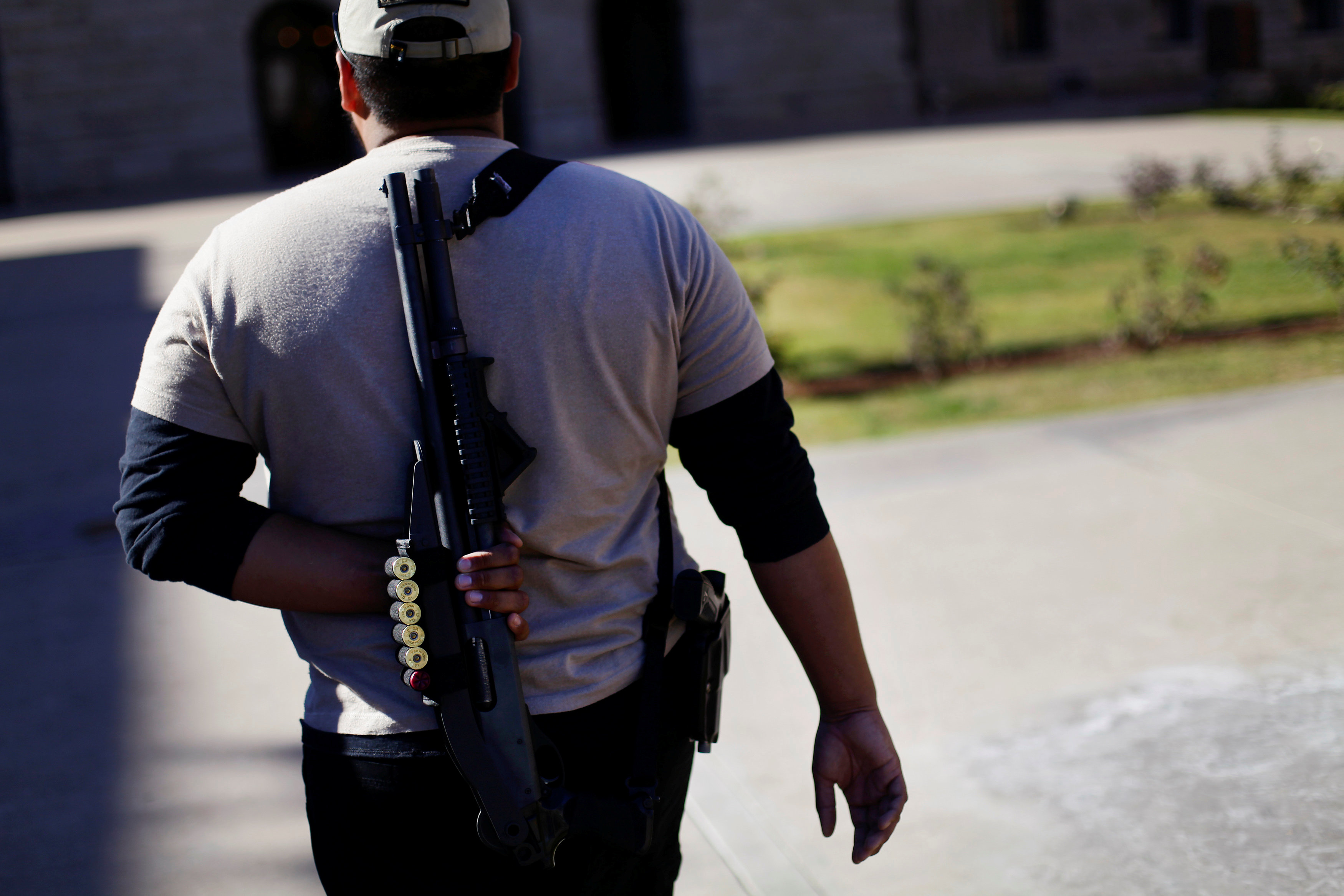 FILE PHOTO: A man walks with his Remington 870 Express 12 gauge shotgun during a pro-gun and Second Amendment protest outside the Arizona State Capitol in Phoenix, Arizona, U.S., January 19, 2013. REUTERS/Joshua Lott/File Photo