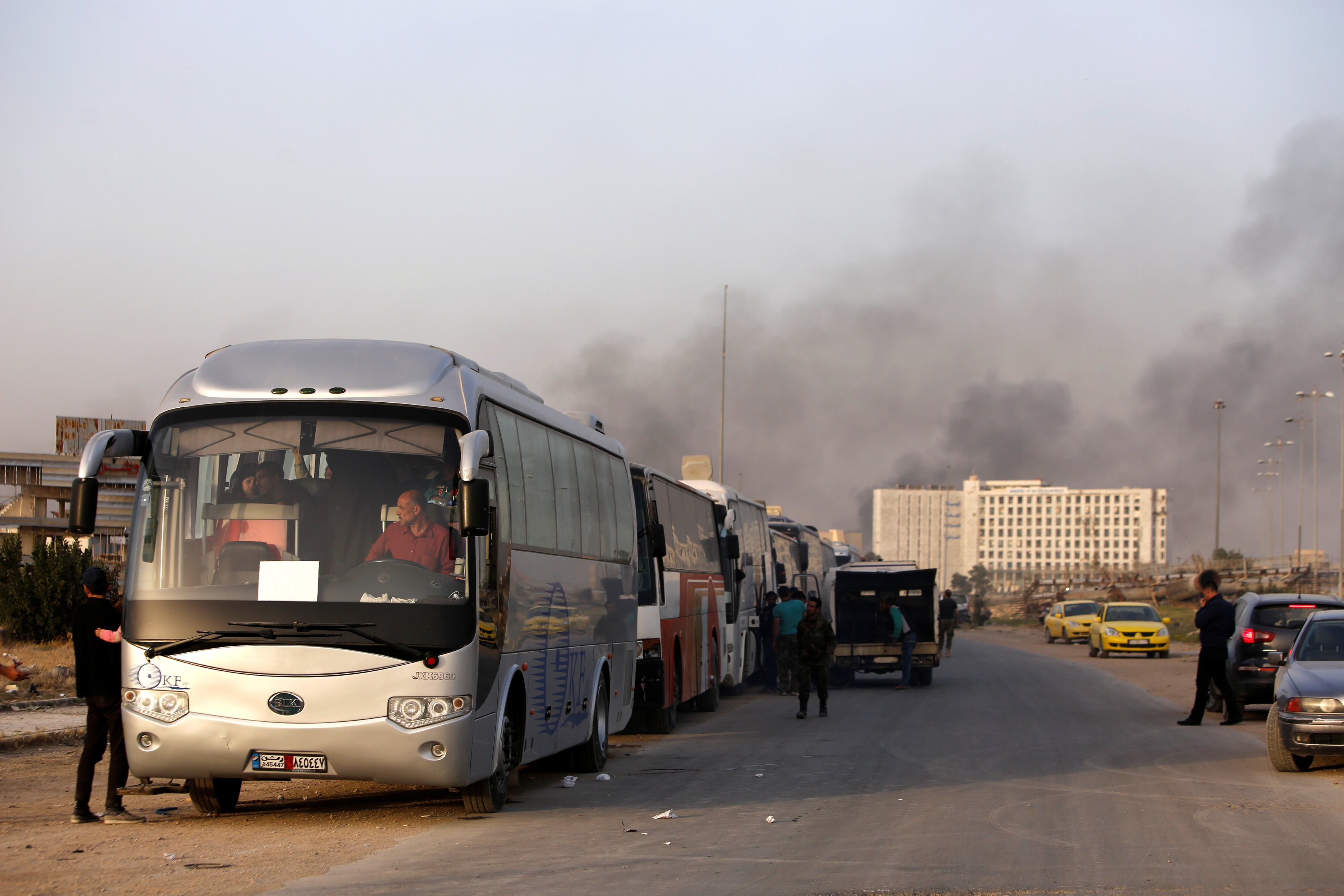 A convoy of buses that carry rebels and their families waits at Harasta highway outside Jobar, in Damascus, Syria March 26, 2018. REUTERS/Omar Sanadiki
