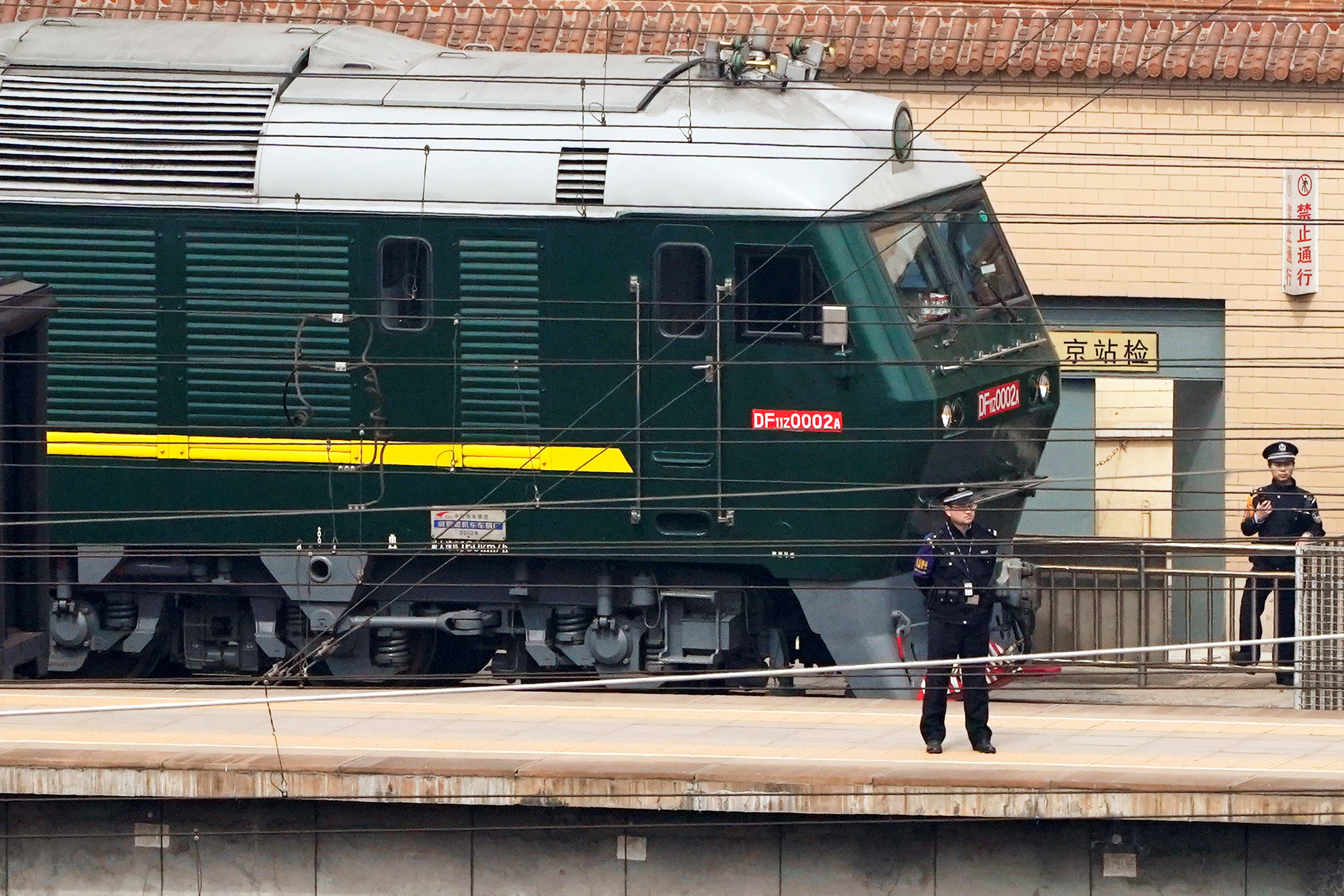 Police officers keep watch next to a train at the Beijing Railway Station in Beijing, China March 27, 2018. REUTERS/Jason Le