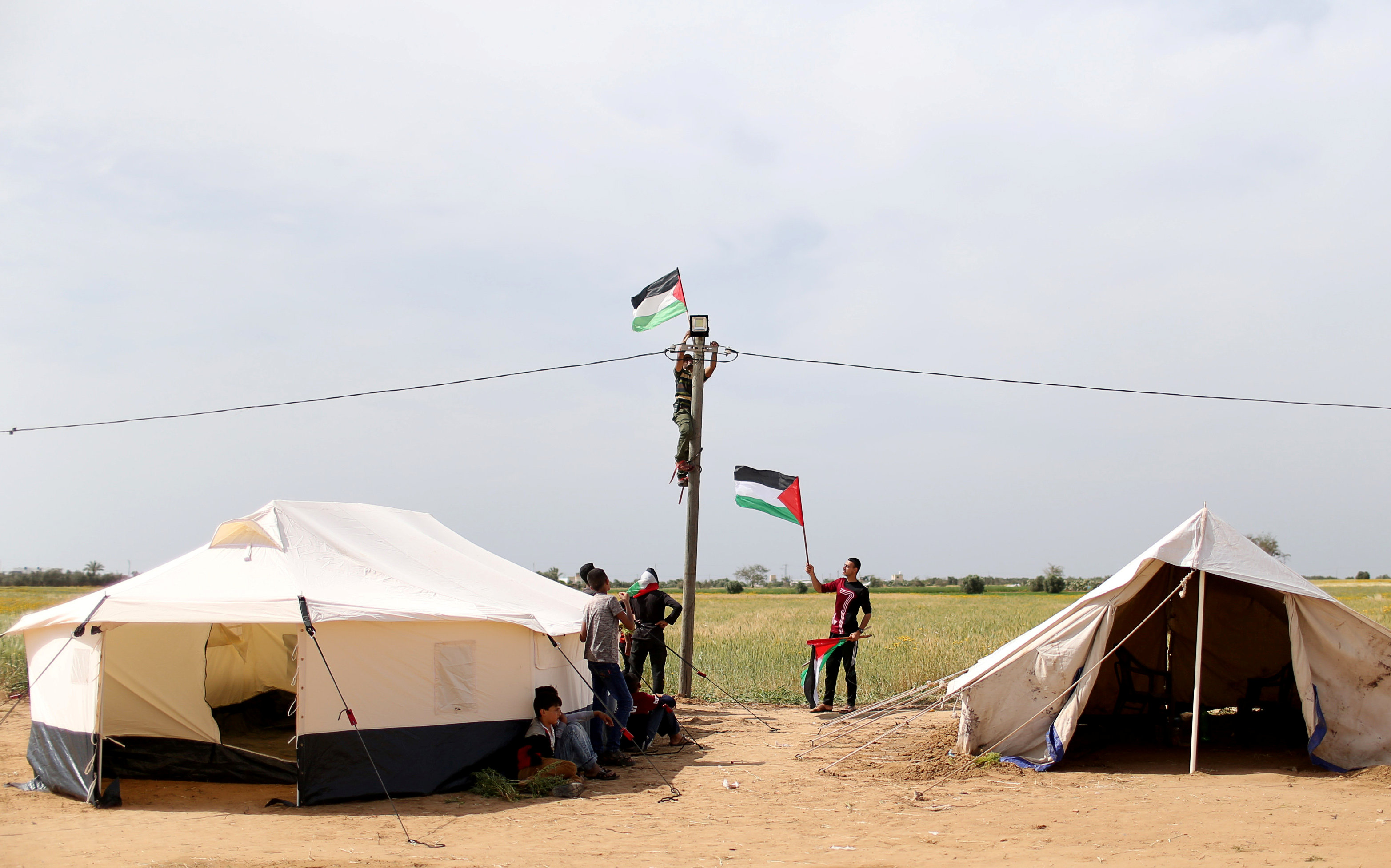 A man hangs a Palestinian flag at an electric pole near the border with Israel, in the southern Gaza Strip March 28, 2018. REUTERS/Ibraheem Abu Mustafa