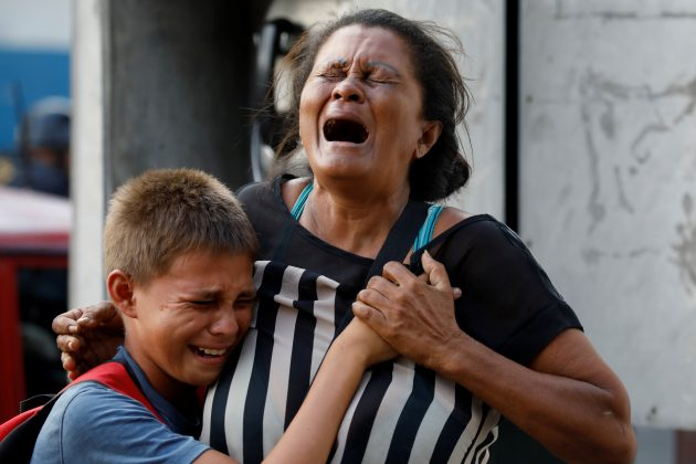 Relatives of inmates held at the General Command of the Carabobo Police react as they wait outside the prison, where a fire occurred in the cells area, according to local media, in Valencia, Venezuela March 28, 2018. REUTERS/Carlos