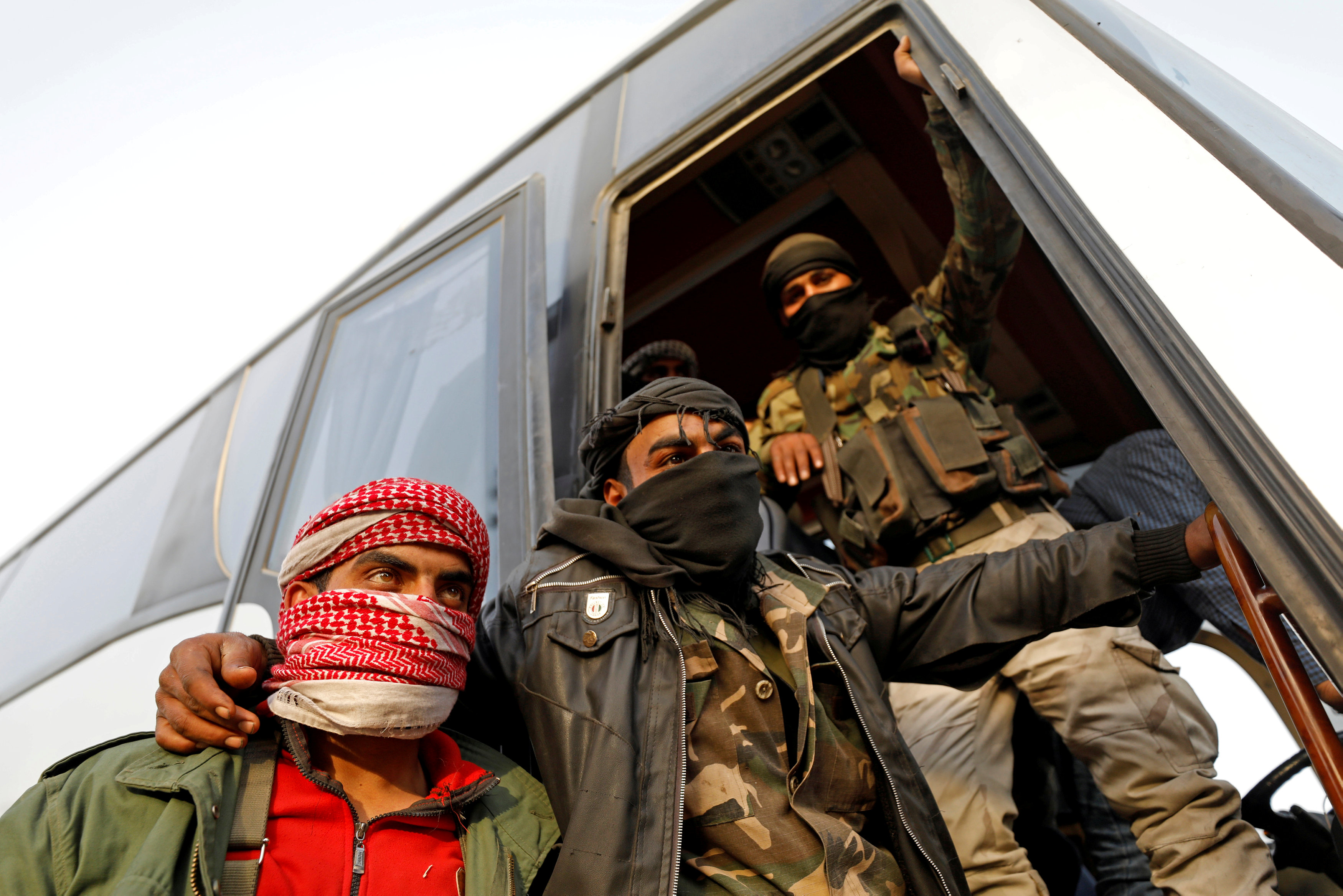 FILE PHOTO: Rebel fighters gesture as they stand next to a bus before their evacuation, at Harasta highway outside Jobar, in Damascus, Syria March 26, 2018. REUTERS/Omar Sanadiki/File Photo