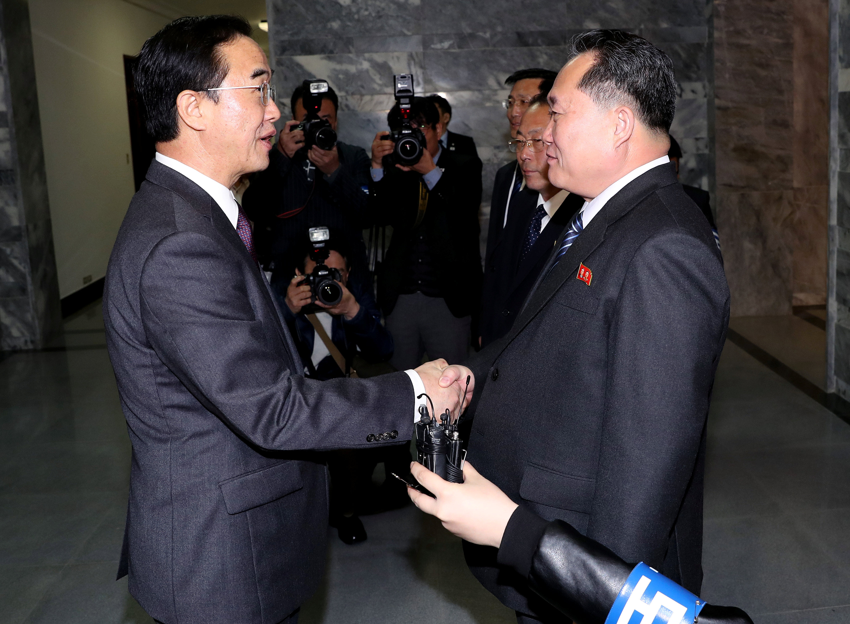 South Korean Unification Minister Cho Myoung-gyon is greeted by his North Korean counterpart Ri Son Gwon as he arrives for their meeting at the truce village of Panmunjom, North Korea, March 29, 2018. Korea Pool/Yonhap via REUTERS