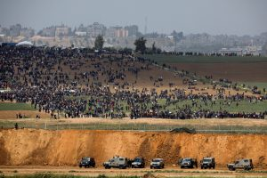 Israeli military vehicles are seen next to the border on the Israeli side of the Israel-Gaza border, as Palestinians demonstrate on the Gaza side of the border, March 30, 2018. REUTERS/Amir Cohen