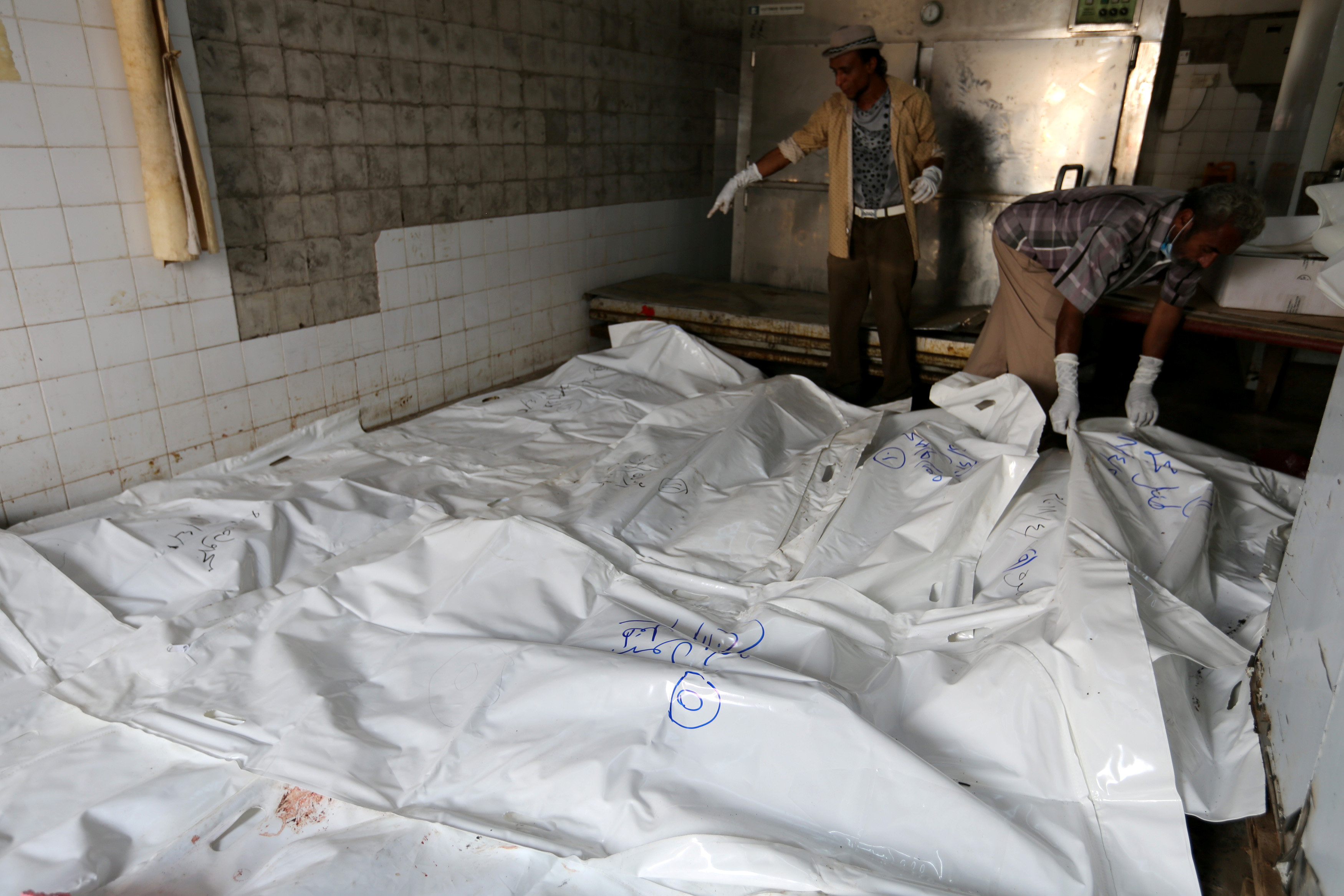 Morgue workers sort plastic bags containing bodies of an airstrike victims in Hodeida, Yemen April 2, 2018. REUTERS/Abduljabbar Zeyad
