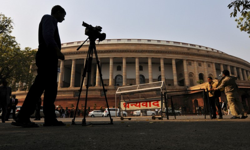 FILE PHOTO: Television journalists report from the premises of India's Parliament in New Delhi, India, February 13, 2014. REUTERS/Adnan Abidi/File Photo