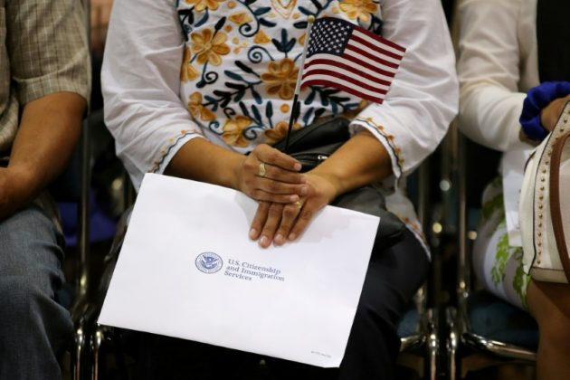 FILE PHOTO: An attendee holds her new country's flag and her naturalization papers as she is sworn in during a U.S. citizenship ceremony in Los Angeles, U.S., July 18, 2017. REUTERS/Mike Blake/File Photo