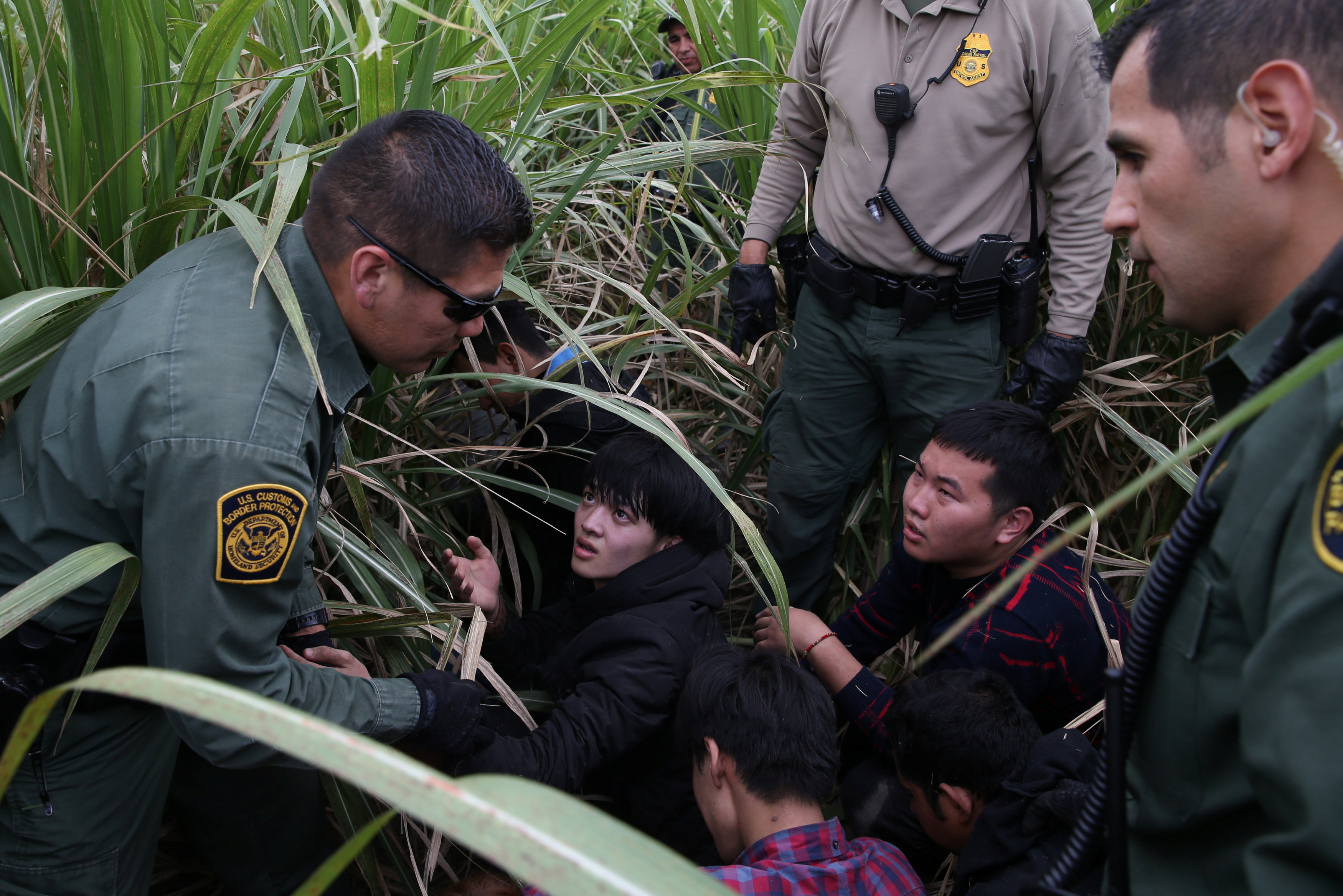 Border patrol agents apprehend immigrants who illegally crossed the border from Mexico into the U.S. in the Rio Grande Valley sector, near McAllen, Texas, U.S., April 3, 2018. REUTERS/Loren Elliott