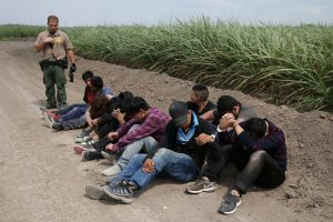 A border patrol agent apprehends immigrants who illegally crossed the border from Mexico into the U.S. in the Rio Grande Valley sector, near McAllen, Texas, U.S., April 3, 2018. REUTERS/Loren Elliot